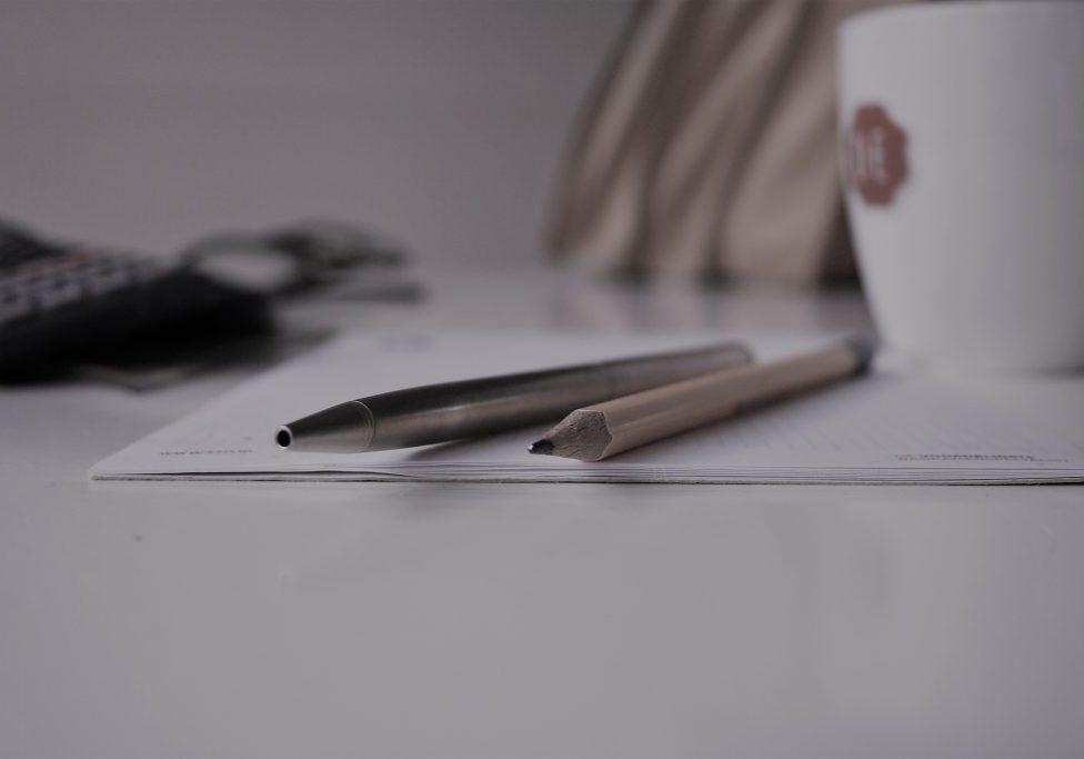 potloden op notitieblok met mok koffie tijdens grip op leren bijles
